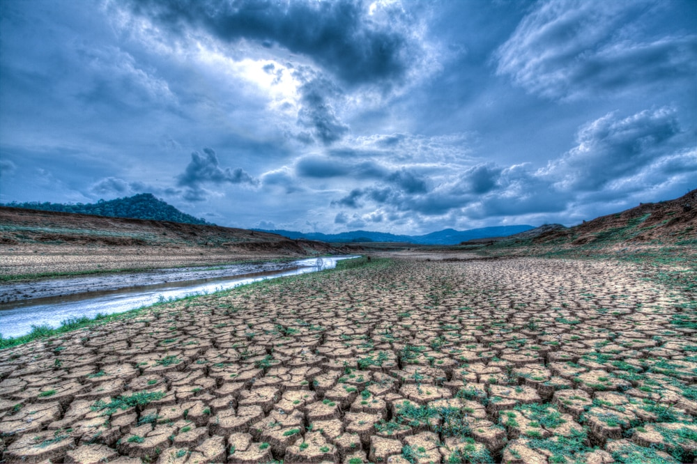 Cracked, parched earth in foreground, dramatic clouds in background