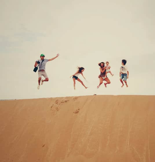 A family jumping on the sand