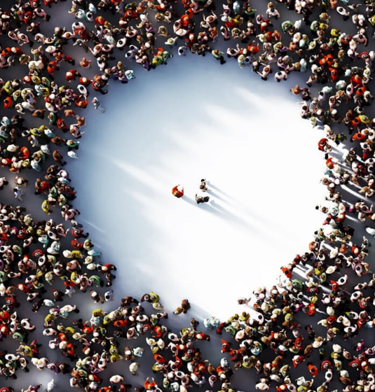 Three people stood in the middle of a large circle of people