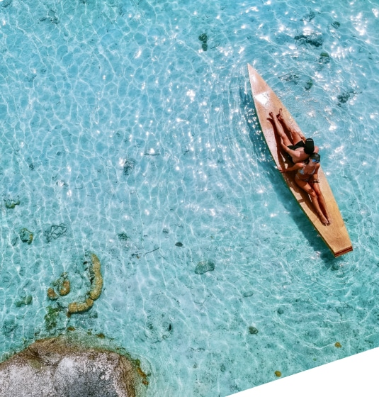 Two people sat on a wooden canoe in a lake