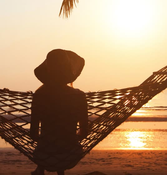 A woman sitting in a hammock looking out to sea