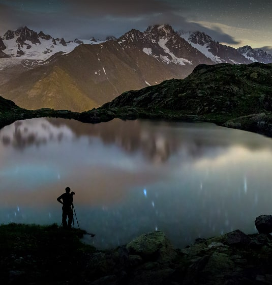 Man with camera looking into lake